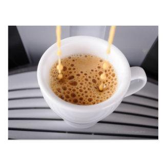 Café express que vierte en la taza tarjeta postal