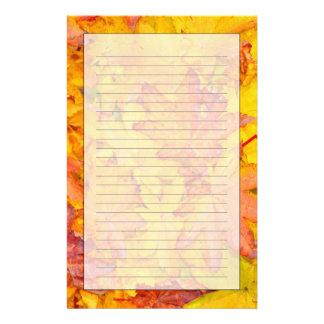 Caída decorativa roja y amarilla de las hojas de  papeleria