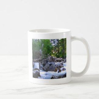 Caídas del río de la montaña del agua taza de café