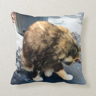 calico cat licking hind legs throw pillow