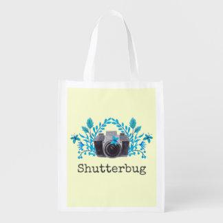 Cámara del Shutterbug con las hojas y las Bolsas Para La Compra