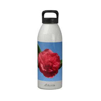 Camelia roja en cielo azul botella de agua