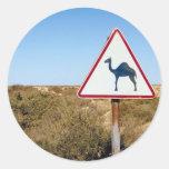 Camellos amonestadores a continuación etiqueta redonda