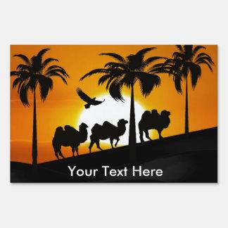 Camellos del desierto en la puesta del sol letreros