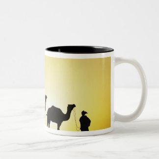 Camellos y conductor del camello silueteado en la  tazas de café
