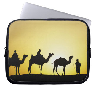 Camels and camel driver silhouetted at sunset, 2 laptop sleeve