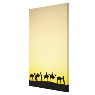 Camels and camel driver silhouetted at sunset, 4 canvas print