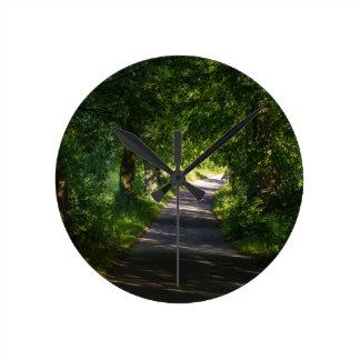 Camino romántico en el paisaje del bosque reloj redondo mediano