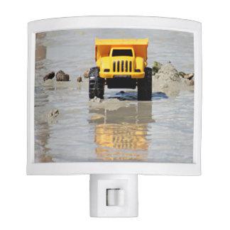 Camión amarillo del juguete en el agua poco luz de noche