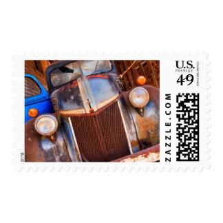 Camión oxidado viejo en una granja timbres postales