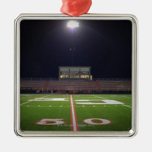 Campo de fútbol americano iluminado en la noche adorno navideño cuadrado de metal