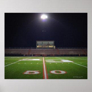 Campo de fútbol americano iluminado en la noche posters
