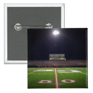 Campo de fútbol americano iluminado en la noche pin