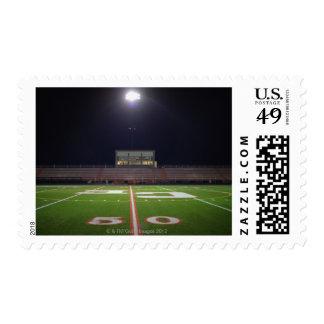 Campo de fútbol americano iluminado en la noche sello