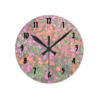 Campo de las flores anaranjadas rosadas púrpuras d reloj redondo mediano