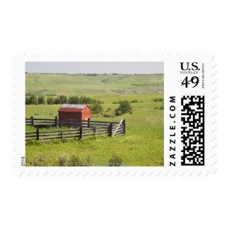 Campos del pasto con una cabaña roja y un área sellos