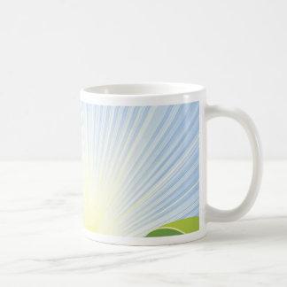 Campos verdes idílicos con los rayos de la sol y s tazas de café