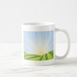 Campos verdes idílicos con los rayos de la sol y s taza de café