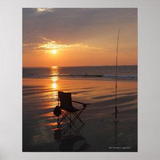 Caña de pescar y silla por el océano en el tempran póster