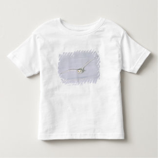 Canada, Quebec. Snowy owl flies low over snow. Toddler T-shirt