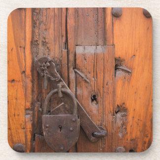 Candado en puerta de madera posavasos de bebidas