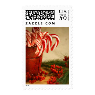 Candy canes in red tin can with berries postage