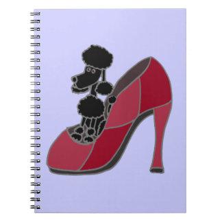 Caniche negro que se sienta en un zapato rosado de libreta espiral