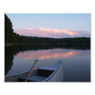 Canoa, paleta y lago en la puesta del sol cojinete