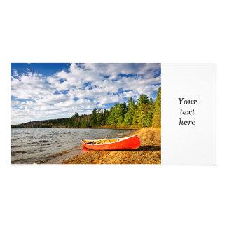 Canoa roja en orilla del lago tarjetas fotograficas