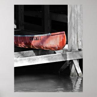 Canoa roja vieja en una casa barco de madera póster