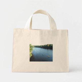 Canoe in blue water mini tote bag