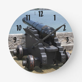 Canon sobre castillo empareda reloj redondo mediano