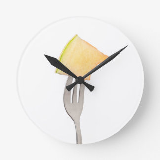 Cantaloupe held by a fork round clock