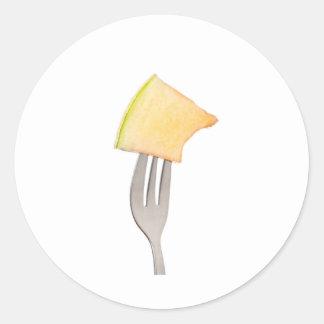 Cantalupo sostenido por una bifurcación pegatina redonda