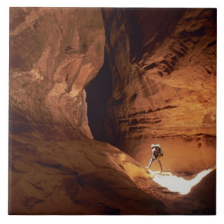 Canyoneer illuminated in the depths of a narrow ceramic tile