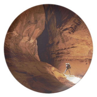 Canyoneer illuminated in the depths of a narrow plate