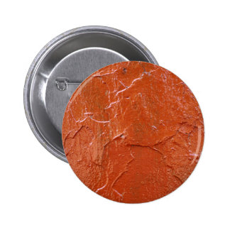 Capa gruesa y desigual de pintura roja en una pin redondo 5 cm