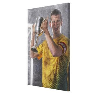 Capitán del fútbol que soporta la taza del trofeo  lona estirada galerías
