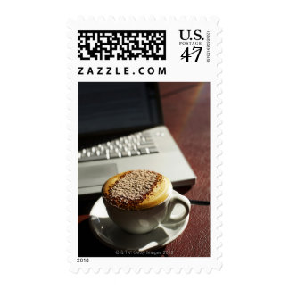 Cappuccino in front of laptop postage