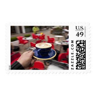 Cappucino being served at outdoor cafe. postage stamp