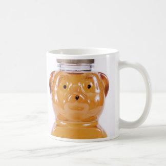 Cara de oro 2 del oso de miel echada a un lado taza de café