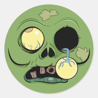 Cara del zombi con el ojo haciendo estallar hacia etiqueta redonda