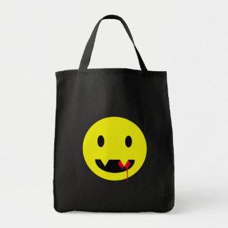 Cara feliz con los colmillos y las camisetas de la bolsa tela para la compra