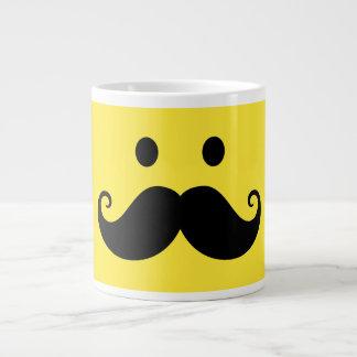 Cara sonriente amarilla de la diversión con el big taza de café grande