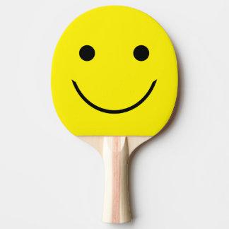 Cara sonriente amarilla pala de ping pong