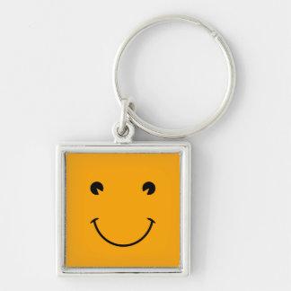 Cara sonriente anaranjada llavero cuadrado plateado