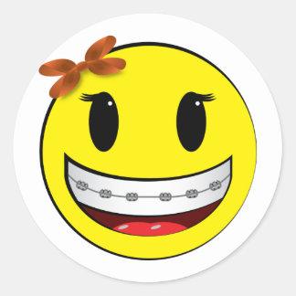 Cara sonriente con los apoyos - chica pegatina redonda