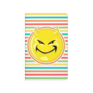 Cara sonriente del diablo en rayas brillantes del cuaderno grapado