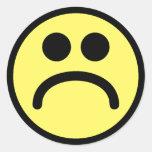 Cara sonriente triste amarilla etiqueta redonda