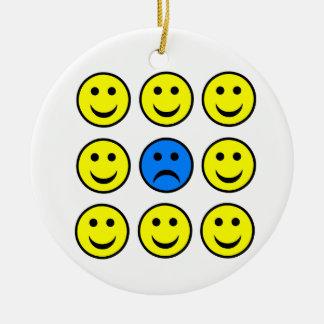 Cara sonriente triste en una muchedumbre de adorno navideño redondo de cerámica